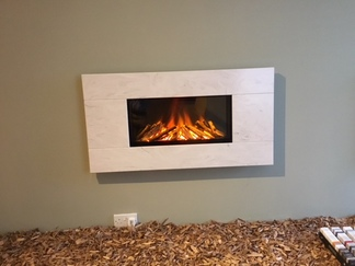 Newdawn 1100 electric fire shown in Limestone Prima, flat wall fix, no recess required, simply hang on the wall - On display in our showroom